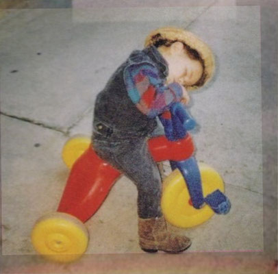 Nick taking a nap on his tricycle.