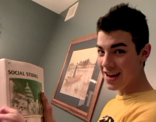 Showing feeling his schoolwork, holding up his pack of 10th Grade Social Studies ACE Paces - From the 2006 Day in the Life video