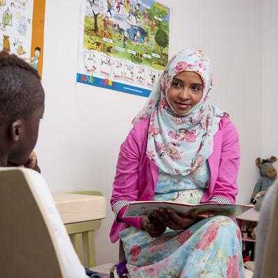 Eine Frau mit Kopftuch hat eine Broschüre auf dem Schoss und blickt einen Jungen ihr gegenüber.