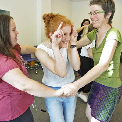 Drei Frauen spielen ein Spiel und lachen.