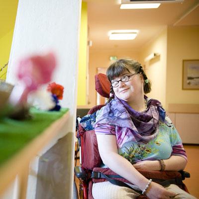 Eine Frau im Rollstuhl lächelt und schaut aus dem Fenster.