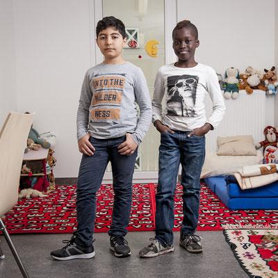 Zwei Jungen im Grundschulalter stehen und schauen in die Kamera.
