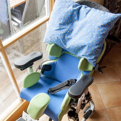 Ein Rollstuhl, in dem ein Kissen liegt.