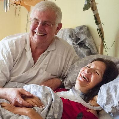 Eine Frau liegt in einem Pflegebett. Ein Mann sitzt neben ihr und hält ihre Hand. Beide lachen.