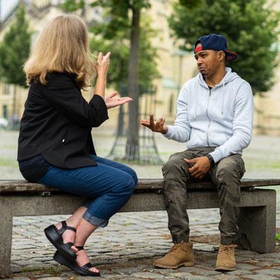 Zwei Personen sitzen auf einer Bank und unterhalten sich in Gebärdensprache.