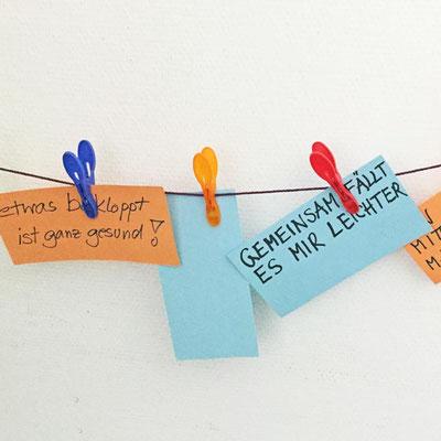 Kleine Schilder mit Sprüchen hängen auf einer Leine.