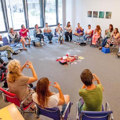 Eine Gruppe sitzt im Kreis in einem Seminarraum.