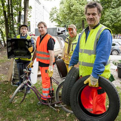 Vier Männer in Arbeitskleidung stehen draußen und haben verschiedene Geräte in den Händen.