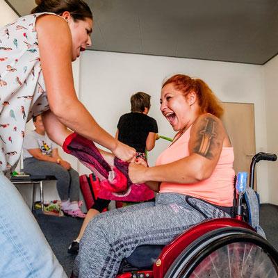 Ein Frau im Rollstuhl kämpft mit einer Frau die steht.
