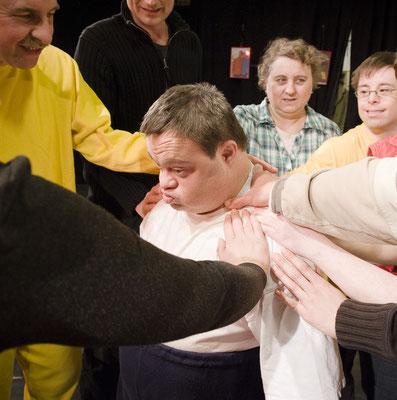 Ein Mann steht in der Mitte. Mehrere Personen stehen um ihn herum und halten ihn fest.
