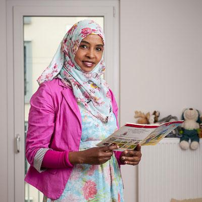 Eine Frau mit Kopftuch hat eine Broschüre in der Hand, schaut in die Kamera und lächelt.