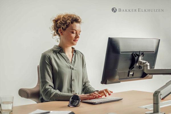 femme qui travaille sur ordinateur avec une souris ergonomique
