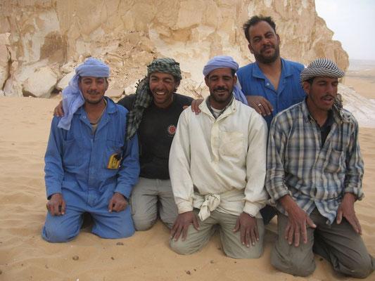 Essam, notre guide, en T-shirt noir; les cuistots, en salopette bleue; les chameliers.