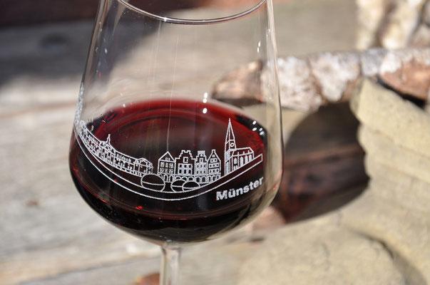 """Fotografie von einem gravierten Weinglas mit Rotwein. Funkenflug Design aus Münster für """"Münster Souvenirs""""."""