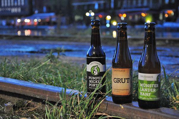 """Fotografie von drei Bierflaschen am Wasser in der Abendstimmung. Funkenflug Design aus Münster für """"Münster Souvenirs""""."""