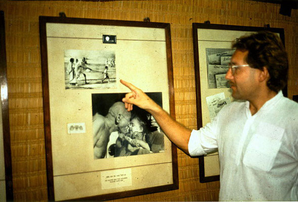 "Peter Rühe pointing out the photograph that often is wrongly captioned as ""The Leader being led"". Peter got it confirmed from the small boy in the picture, Gandhi's grandson Kahandas (""Kanaa"", ""Kanu"") , that it were two lathi sticks in the picture and Gan"