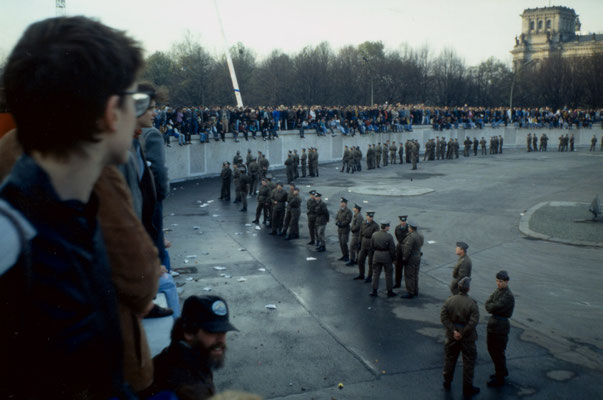The day before the Berlin Wall fell: West-Berliners occupy the wall, confronted with East-German soldiers, 1989.
