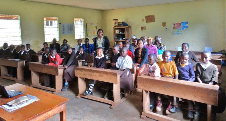 Fr. Kiwara und die Empfänger in der Materuni-Grundschule.