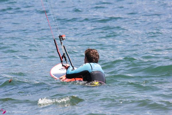 Kitesurfer schwimmt mit Kiteboard