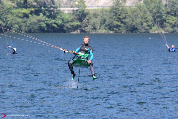 Kitesurfer sitzt auf einem Kitefoil