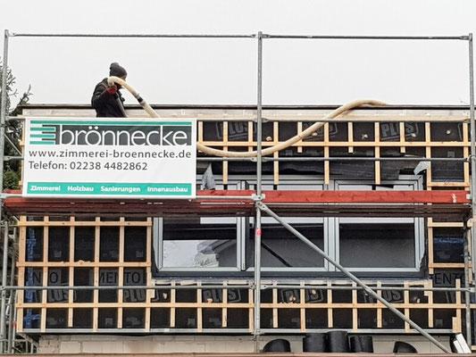 Ein Mitarbeiter der Zimmerei Brönnecke beim Einblasen der Fassadendämmung.