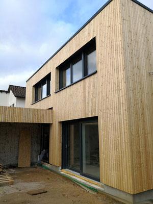 Fertig! Das ganze Haus ist rundherum mit der modernen Holzschalung verkleidet, die Fassade ist ökologisch und perfekt gedämmt.