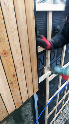 Die Fassadendämmung ist eingeblasen. Nun montieren wir die Holzfassade. Die einzelnen Bretter der Nut-und-Feder-Schalung werden dafür ineinander geschoben.