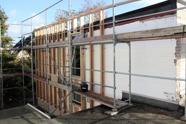 Hier werden Balken auf die Außenmauer montiert. Sie sind die Basis der Hohlräume, in die wir die Holzfaserdämmung einblasen.