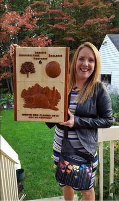 Madame Guyanne Fradette avec la plaque sculptée qui lui a été remise en reconnaissance du prix du plus beau jardin privé de la MRC de Portneuf en 2016.