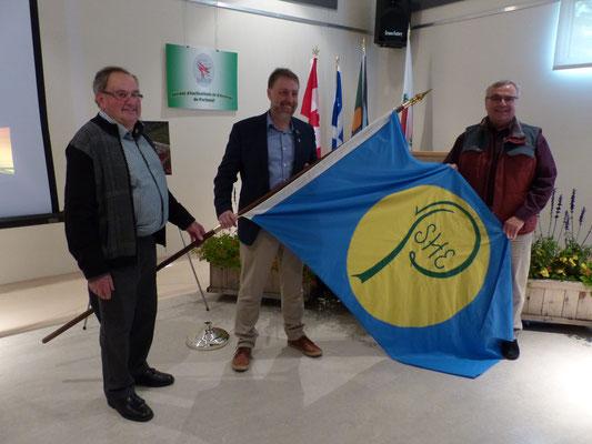 Passation du drapeau de la SHEP: M. Rolland Hamel, président de la SHEP (à gauche);  M. Michel Blackburn, maire de Cap-Santé (au centre) remet le drapeau de la SHEP à M. Gaston Arcand, maire de Deschambault-Grondines (à droite).