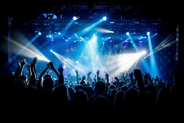 Lichtshow mit bunter Beleuchtung an Traversen als Teil der Veranstaltungstechnik bei einem großen Konzert