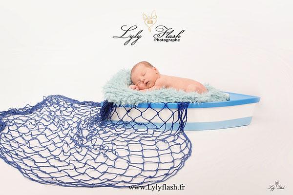bébé dans un petit bateau photographe de naissance près de hyères mer