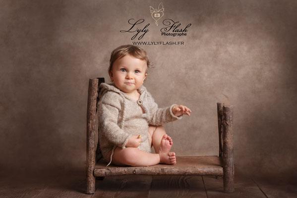 portrait de bébé en studio photo. Photo bébé par photographe lylyflash sur son lit en bois