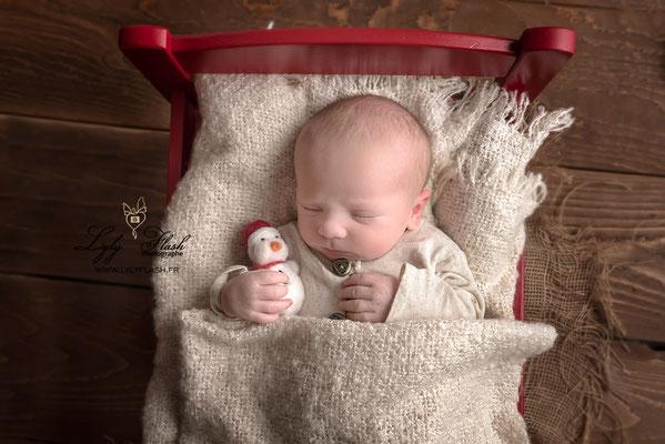 quand bébé dort dans son petit lit rouge, une photo issue du shooting naissance de baby boy par lyly flash photographe du var près de toulon pour noël