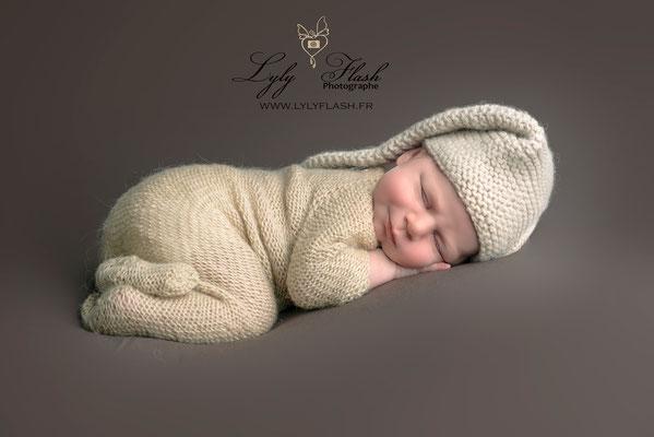 newborn posing sur fond maron bébé qui sourit #photographe #lylyflash photographe bormes les mimosas
