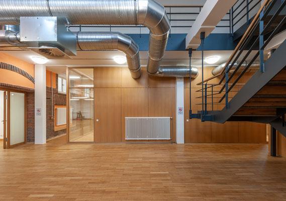 Sanierung und Umnutzung einer historischen Turnhalle zum Nachwuchsleistungszentrum,  Foyer mit lufttechnischen Anlagen und Treppe