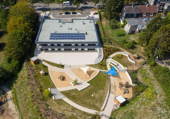 Kita Hatzfelder Straße Wuppertal, Luftaufnahme Ansicht Kindertagesstätte inklusive Blick auf das Dach mit Haustechnik, auf die Kiss & Ride Spur und die Stellplätze