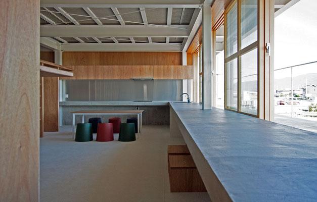居間・食堂 ベランダと一体のコンクリート製キッチンは長さ13m