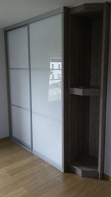Placard portes coulissantes en verre, avec étagères de coin ouvertes.