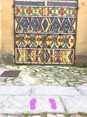 Praktisch: Bunte Fußabdrücke zeigen den Weg zu allen Kunstwerken in Aggius