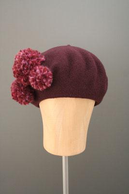 Baske aus Wolle mit Pompoms aus dem eigenen Hutatelier