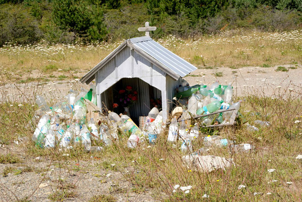 Sanctuary beside the road. The saint is a women who died because of water. That's why the people leave water bottles beside it. They say it brings luck!