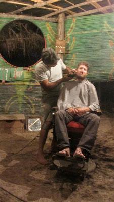 Coiffeur Eber in seinem speziellen Salon an der frischen Luft. // Sam gets a haircut from Eber.