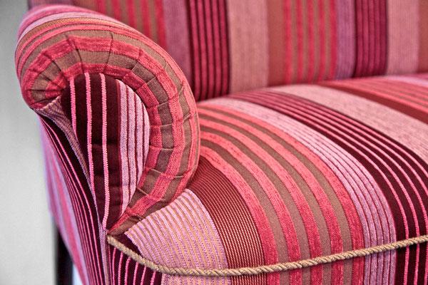 Klassische Faltenbildungen in der Rundungen der Armlehnen, sowie eine farblich abgesetzte Kordel unterstreichen in kleinen Details den neuen Look. Moderne Farben und Formen auf einem alten Möbelstück.