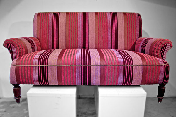 Der alte Bezugsstoff wird durch einen neuen Teflonbezug ersetzt, der durch die unregelmäßigen Streifen und der ausgefallenen Farbkombination den Charme des Sofas wieder unterstreicht.