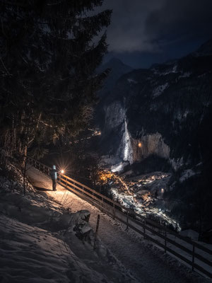 Man with latern above the village Lauterbrunnen in the swiss alp.