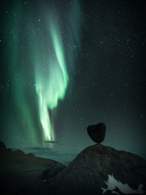 Northern lights appear above the heart-shaped stone at the Uttakleiv in the Lofoten region in Norway.