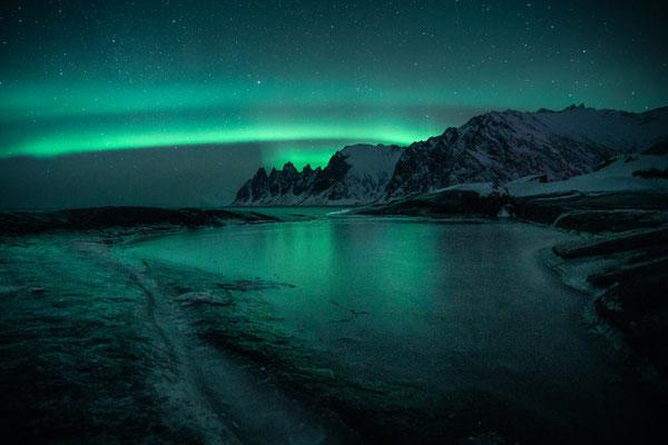 Forzen water reflects the Aurora above Tungeneset in Senja region in Norway.