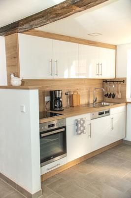 Die Küche ist mit modernen Küchengeräten ausgestattet, die Küchenmöbel von unseren Tischlern gebaut. Auf der rechten Seite steht der Kühlschrank, dort gibt es auch einen Stehtisch mit Hockern.