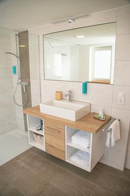 Das großzügige Badezimmer mit ebenerdiger Dusche, WC, großem Spiegel sowie zwei Fenstern.